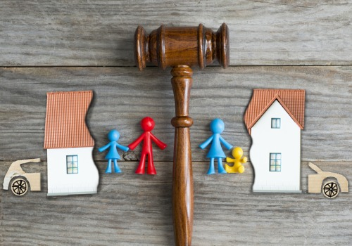 A gavel separating a toy family with a cut-out house and car, representing a divorce attorney in Eureka IL