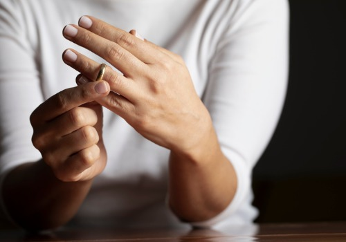 An individual taking off their ring, needing the help of divorce lawyers in Peoria IL