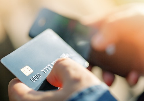 An individual looking up their debt for a credit card, using their phone, soon to need a Bankruptcy Lawyer in Washington IL