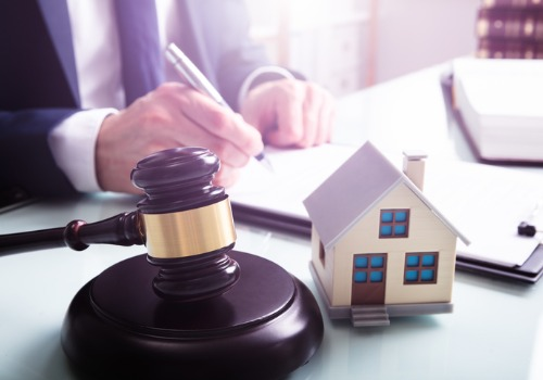 man sitting behind a desk signing a contract with a gavel and house on the desk