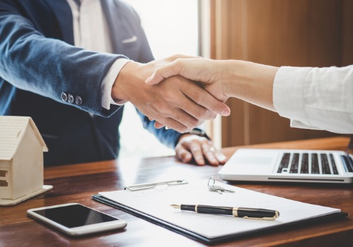 A Real Estate Lawyer in Peoria IL shaking hands with their client