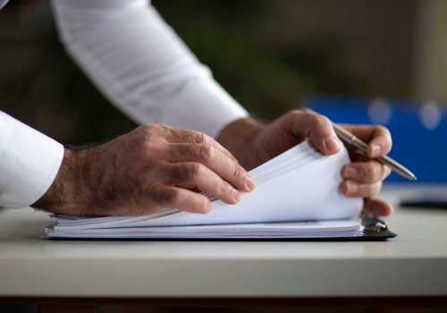 Hands of Real Estate Attorneys in Peoria IL Looking Through Paperwork