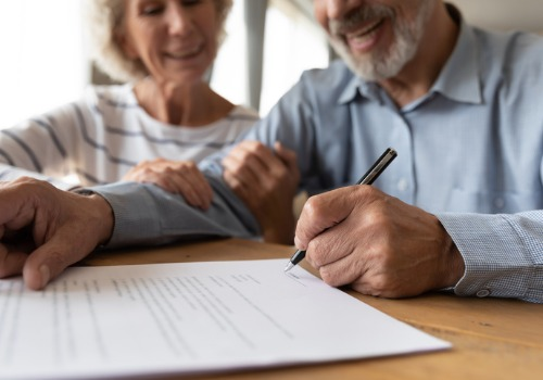An elderly couple signing documents from Estate Planning Attorneys in Peoria IL