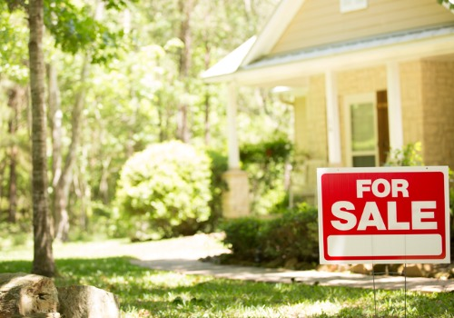 A for sale sign in front of a home in Pekin IL