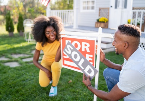 A young couple in front of their newly purchased home, with help from Closing Attorneys in Peoria IL