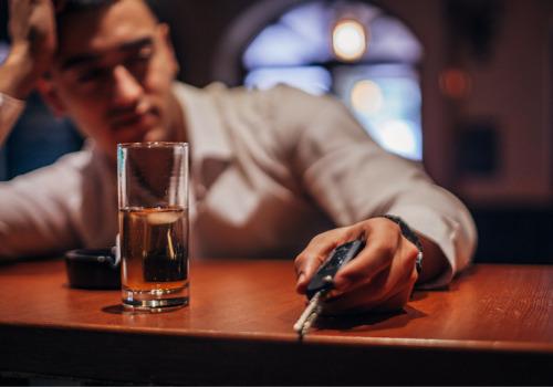 A drunk man at a bar holding his car keys