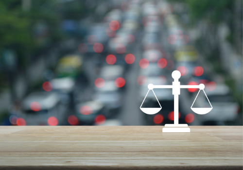 An illustration of a scale in front of a traffic jam, related to a Traffic Lawyer for Washington IL