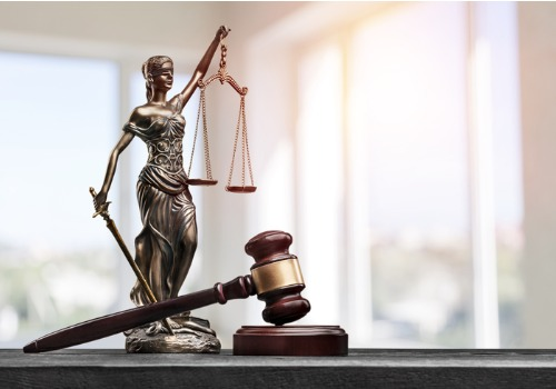 """A gavel next to """"lady justice,"""" representing lawyers for Misdemeanors in Washington IL"""